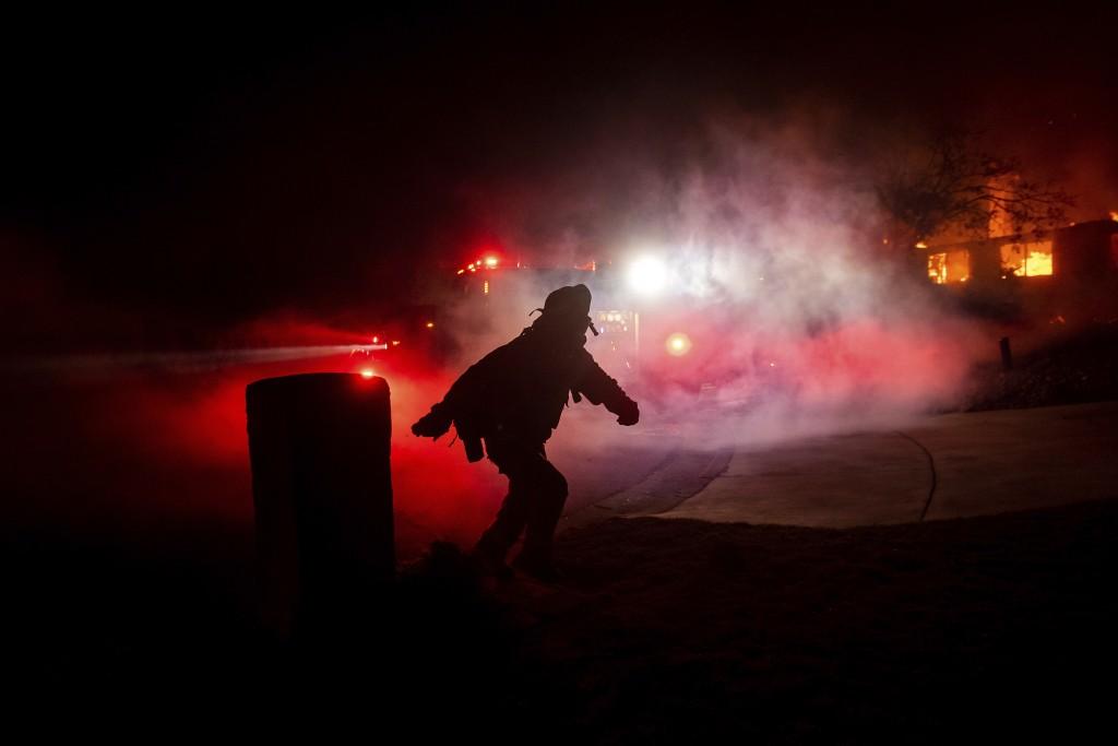 A firefighter runs towards a burning home as the Hillside fire burns through a neighborhood in San Bernardino, Calif., on Thursday, Oct. 31, 2019. The...