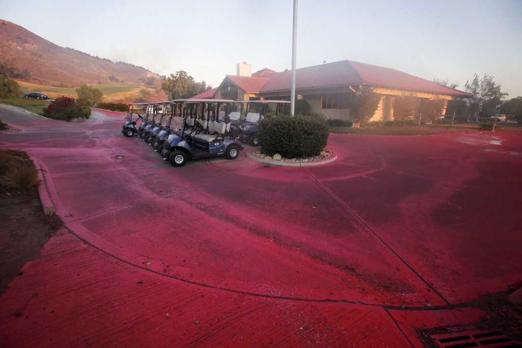 Fire retardant covers the driveway of a golf club in Simi Valley, Calif., Wednesday, Oct. 30, 2019. (AP Photo/Ringo H.W. Chiu)