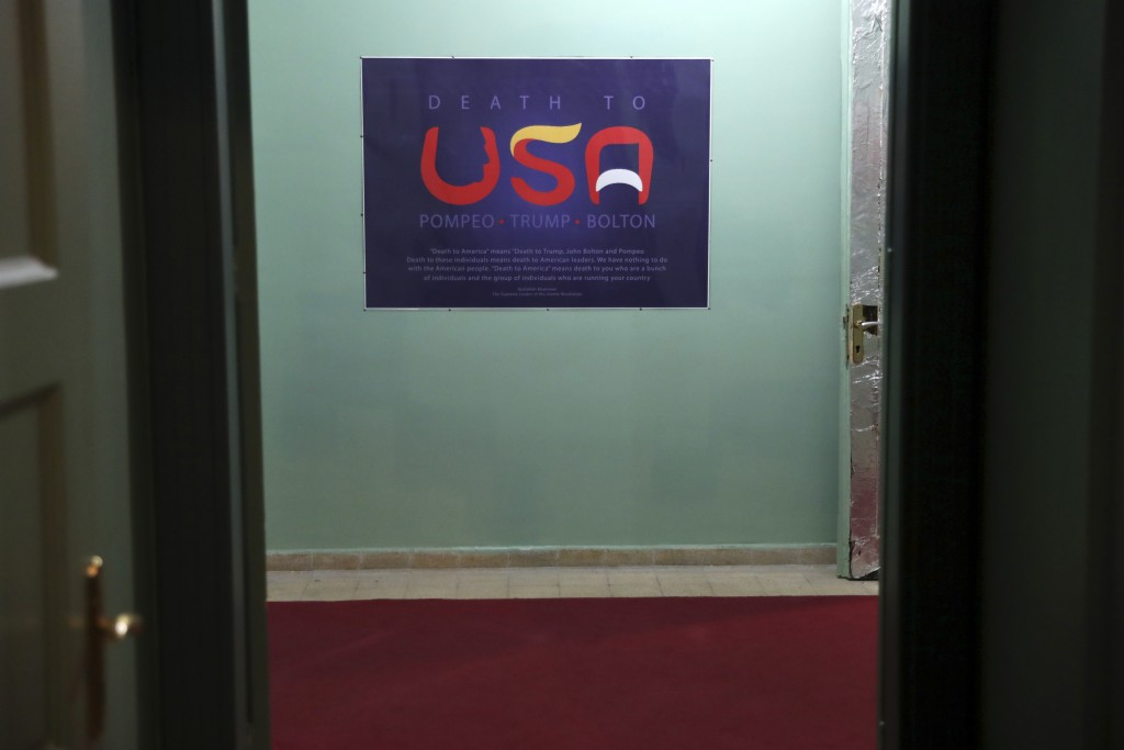 In this Sept. 26, 2019, photo, an anti-U.S. placard adorns a corridor of the former U.S. Embassy in Tehran, now partly a museum, Iran. The slogan in E...