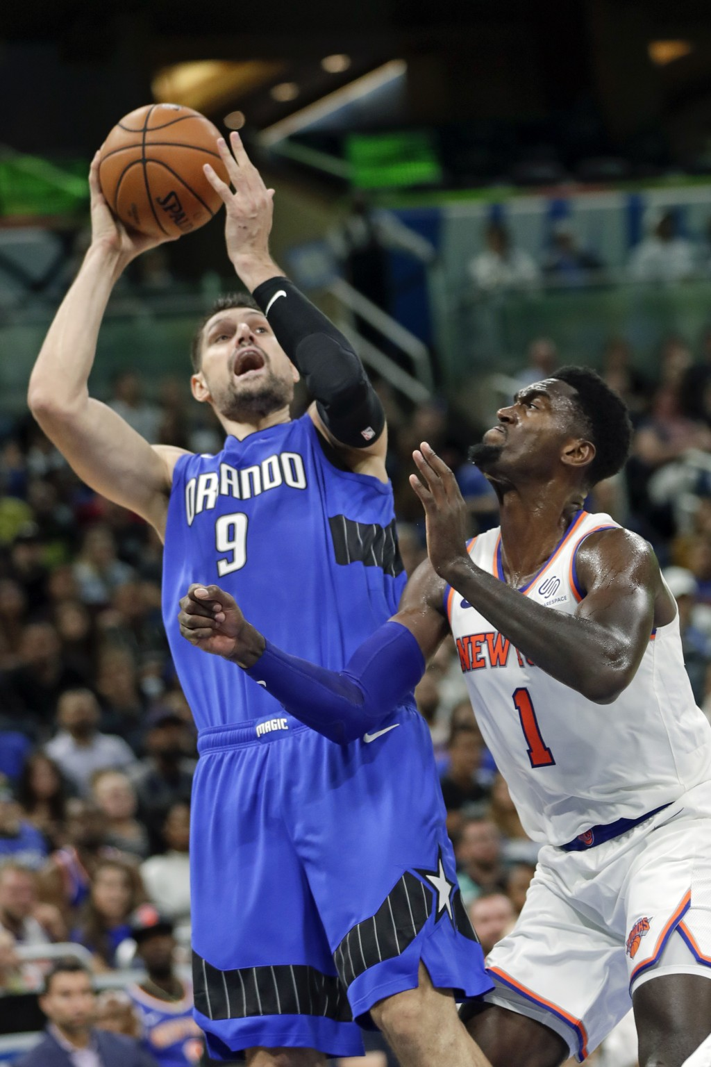 Orlando Magic's Nikola Vucevic (9) takes a shot over New York Knicks' Bobby Portis (1) during the second half of an NBA basketball game, Wednesday, Oc...