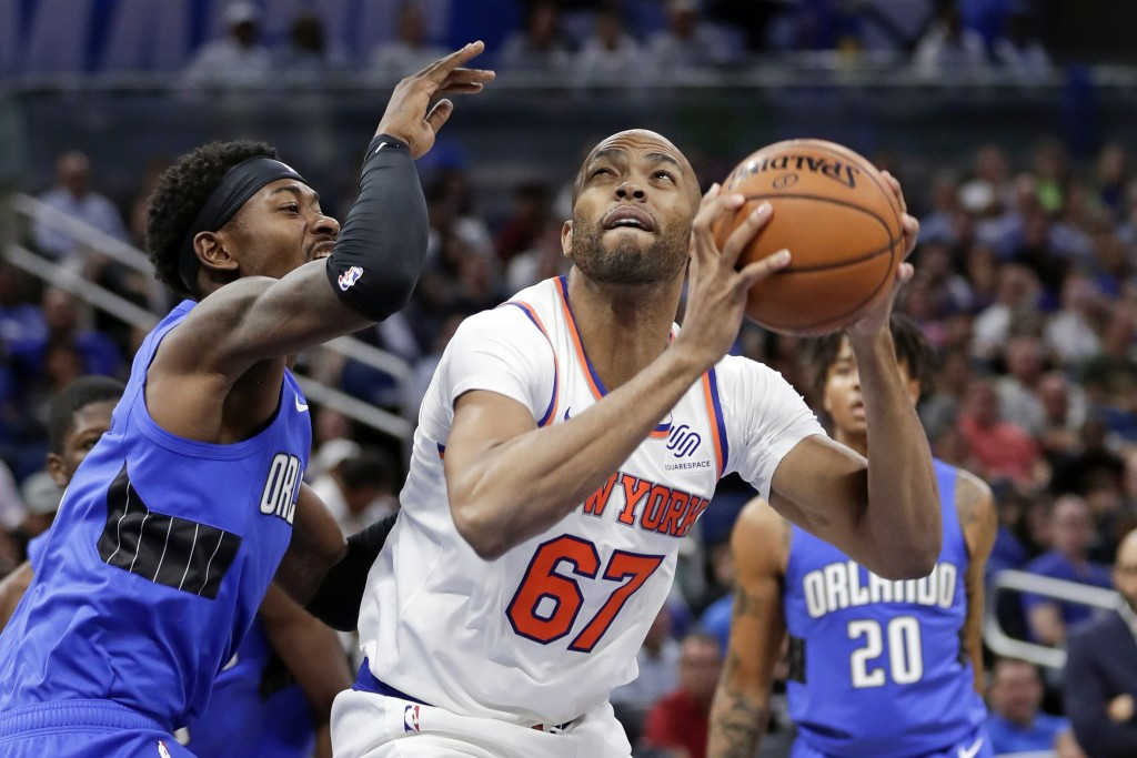 New York Knicks' Taj Gibson (67) looks for a shot against Orlando Magic's Terrence Ross, left, during the first half of an NBA basketball game, Wednes...