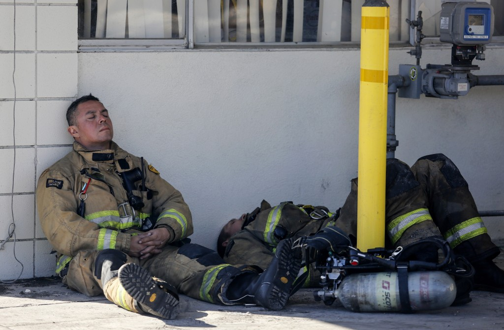 Firefighters rest at outside a cardboard box factory that burned down by a wildfire in Riverside, Calif. Thursday, Oct. 31, 2019. Several blazes broke...