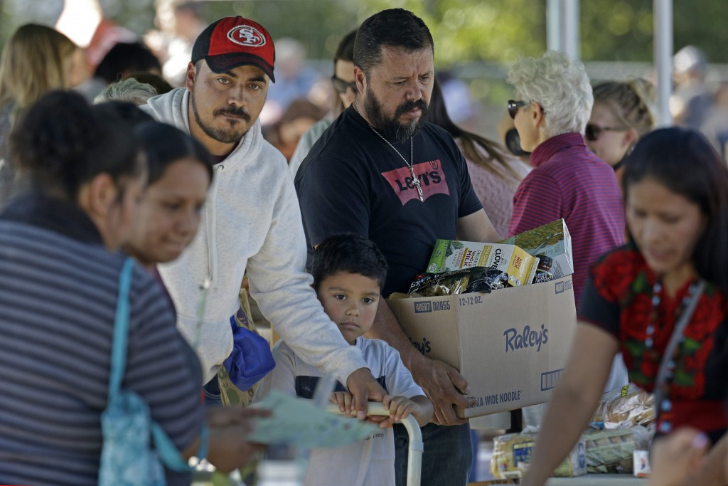 People gather items during a free food distribution for migrant workers evacuated because of the Kincade Fire Thursday, Oct. 31, 2019, in Healdsburg, ...