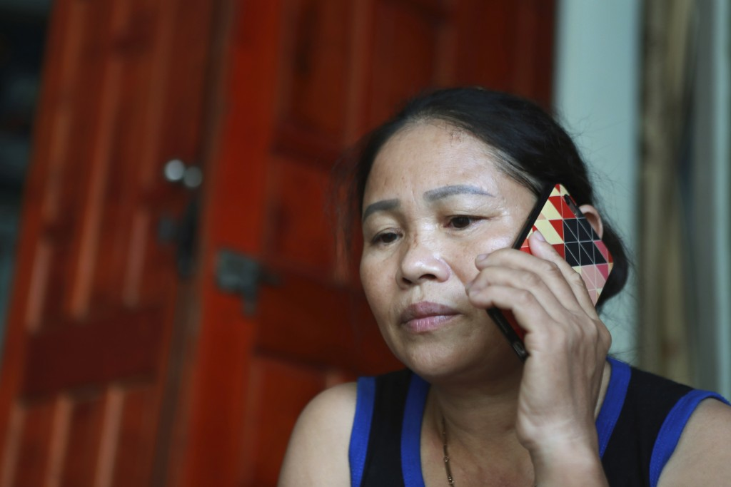 In this Oct. 28, 2019, photo, Hoang Thi Ai, mother of Hoang Van Tiep, who is feared to be among the England truck dead, talks on phone to a relative i...
