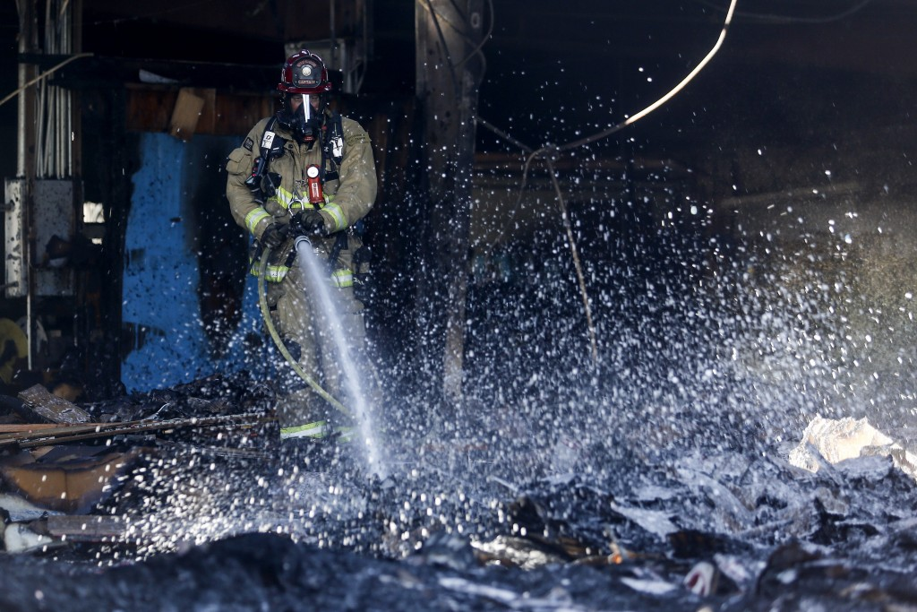 A firefighter puts out hotspots at a cardboard box factory that burned down by a wildfire in Riverside, Calif. Thursday, Oct. 31, 2019.  Several blaze...