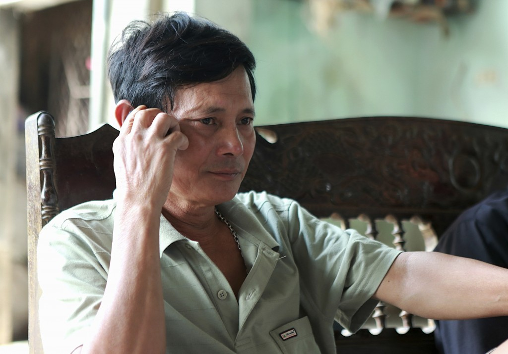 In this Oct. 28, 2019, photo, Hoang Van Lanh, father of Hoang Van Tiep, who is feared to be among the England truck dead, talks on the phone at his ho...