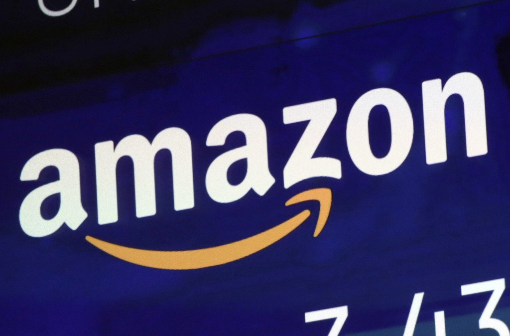 FILE - In this July 27, 2018 file photo, the logo for Amazon is displayed on a screen at the Nasdaq MarketSite in New York. Amazon must decide soon if...