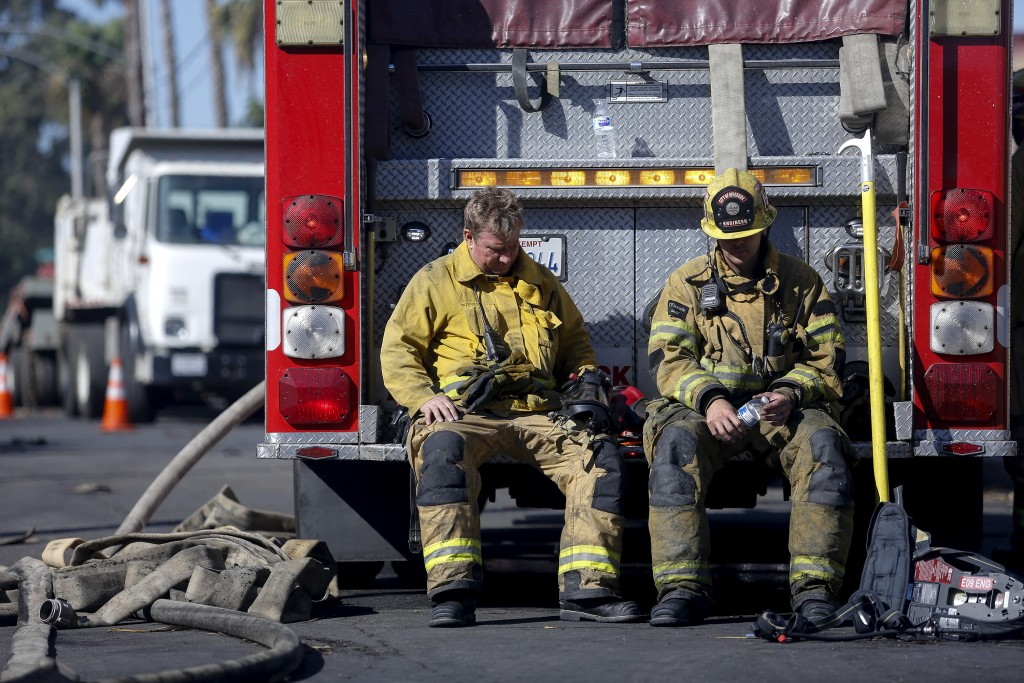 Firefighters rest with their fire truck at outside a cardboard box factory that burned down by a wildfire in Riverside, Calif. Thursday, Oct. 31, 2019...