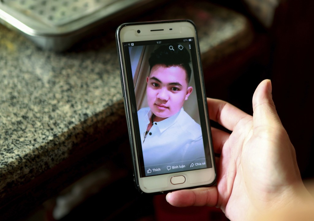 In this Oct. 28, 2019, photo, Hoang Thi Ai, mother of Hoang Van Tiep, who is feared to be among the England truck dead, hold a phone showing a photo o...