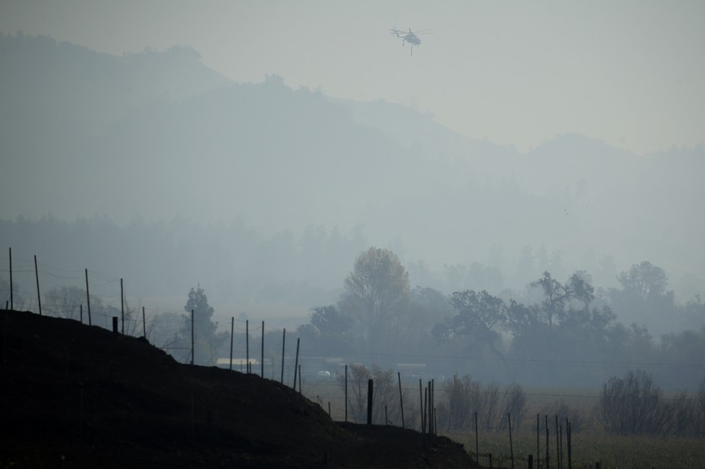 A helicopter flies though a smoky valley carrying water to fight the Kincade Fire near Healdsburg, Calif., Thursday, Oct. 31, 2019. (AP Photo/Charlie ...