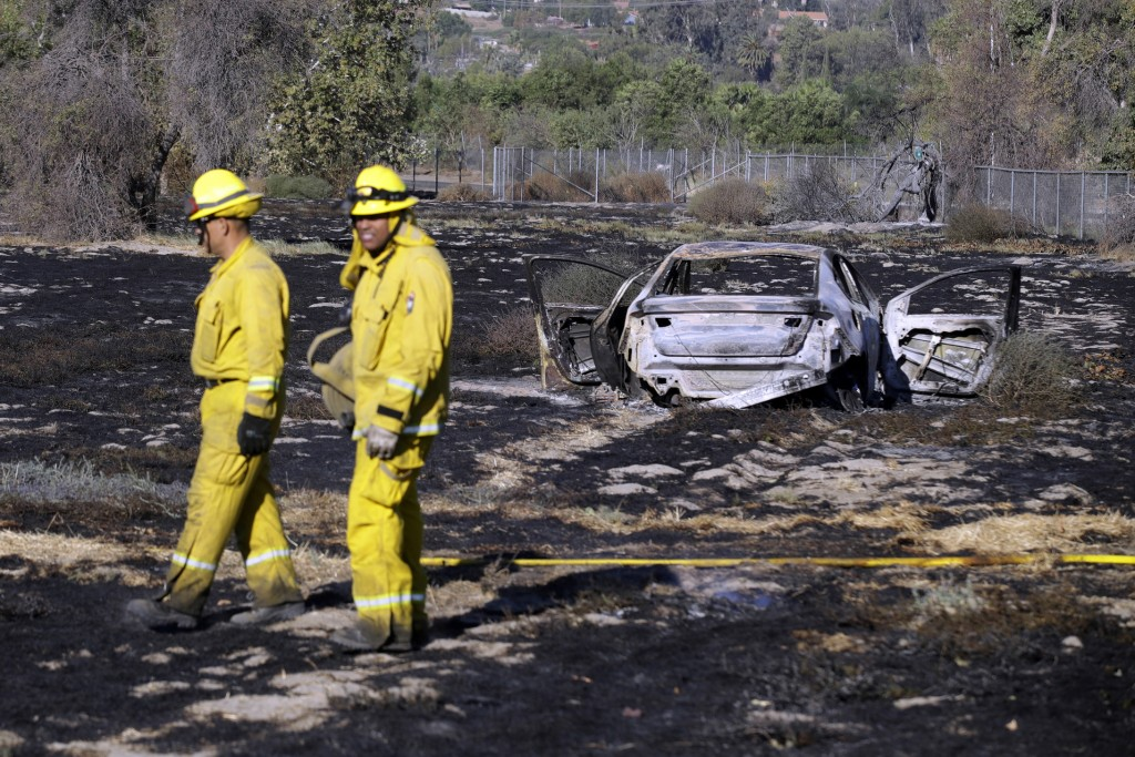 Firefighters stand near a charred vehicle that might started the 46 Fire after a police chase in Rancho Jurupa Park Thursday, Oct. 31, 2019, in Rivers...