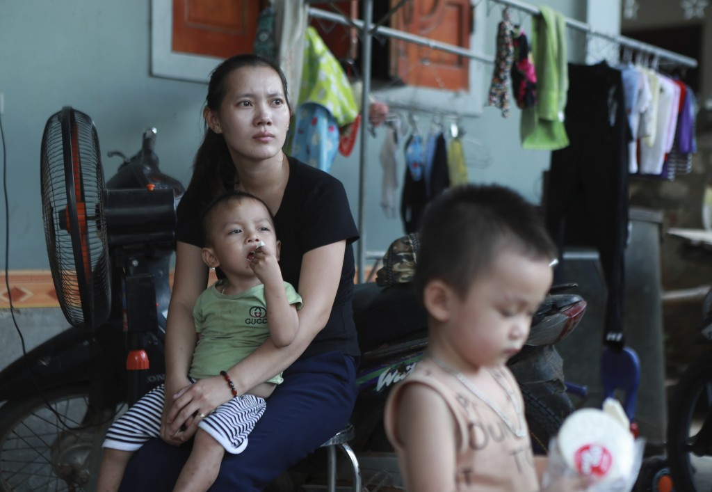 In this Oct.28, 2019, photo, Hoang Thi Nhiem, older sister of Hoang Van Tiep, who is feared to be among the England truck dead, holds her son in Dien ...