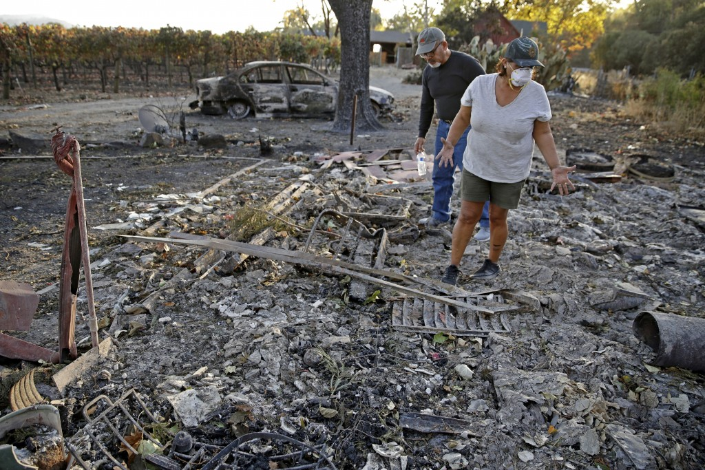 Justo and Bernadette Laos look through the charred remains of the home they rented that was destroyed by the Kincade Fire near Geyserville, Calif., Th...