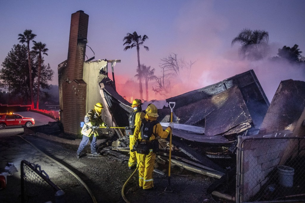 Firefighters mop up at a leveled home as the Hillside Fire burns in San Bernardino, Calif., on Thursday, Oct. 31, 2019. The blaze, which ignited durin...