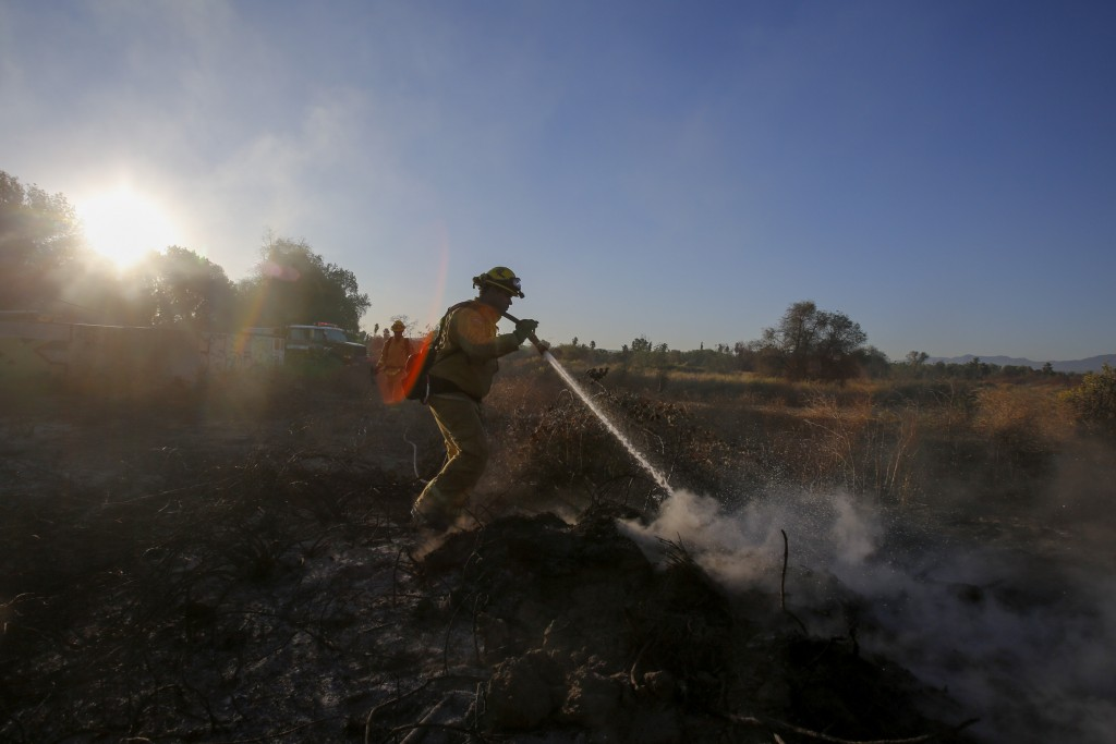 A firefighter puts out hotspots in a wildfire in Riverside, Calif. Thursday, Oct. 31, 2019.   Strong winds fanned new Southern California wildfires on...