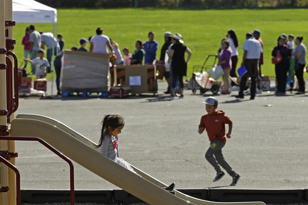 Children play on the playground while people line up for a free food distribution for migrant workers evacuated because of the Kincade Fire Thursday, ...