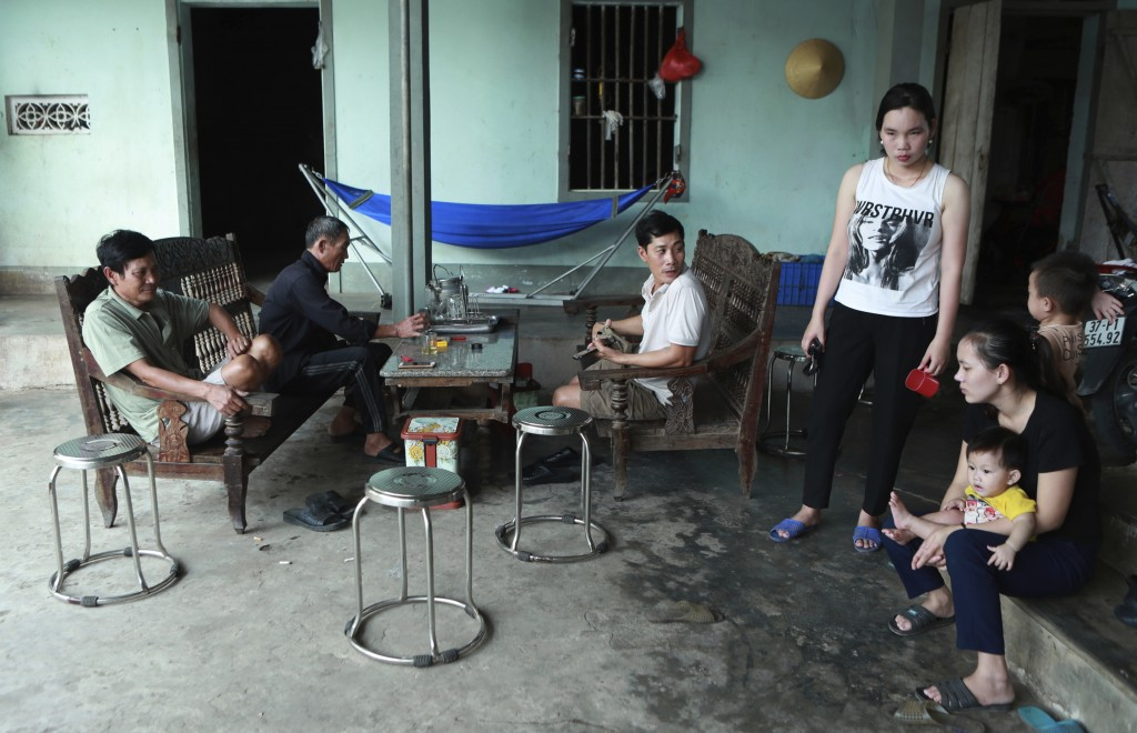 In this Oct. 28, 2019, photo, Hoang Van Lanh, left, father of Hoang Van Tiep, who is feared to be among the England truck dead, sits with his family m...