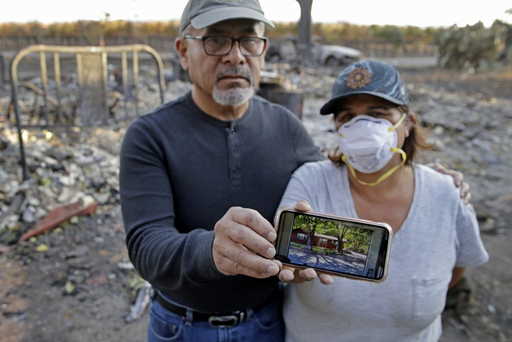 Justo and Bernadette Laos show a photo of the home they rented that was destroyed by the Kincade Fire near Geyserville, Calif., Thursday, Oct. 31, 201...
