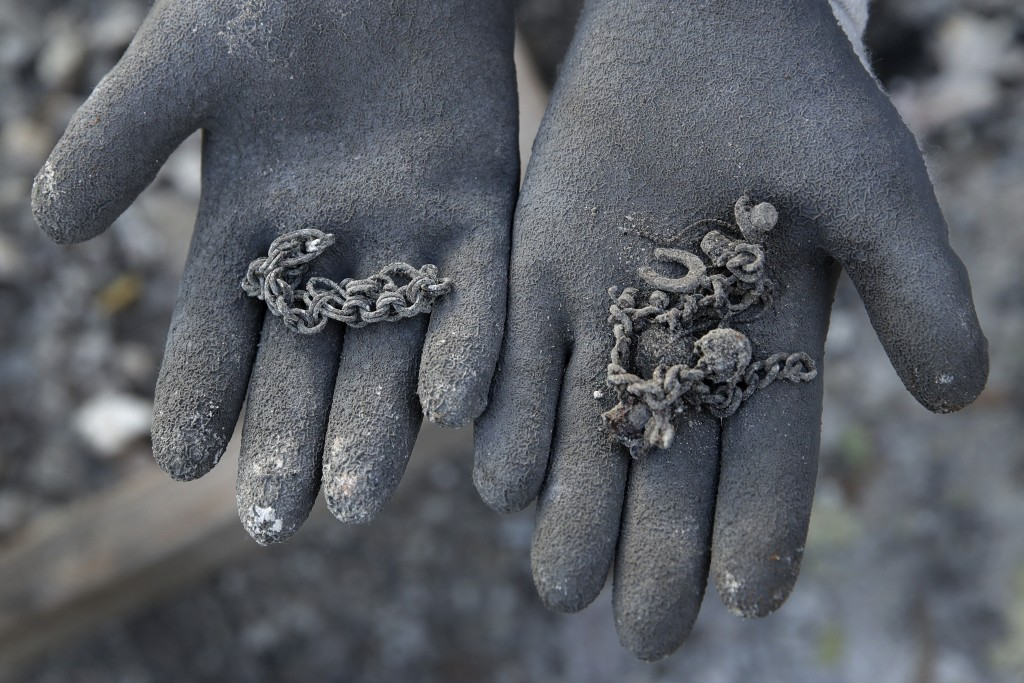 A friend of Bernadette Laos displays jewelry salvaged from her home that was destroyed by the Kincade Fire near Geyserville, Calif., Thursday, Oct. 31...