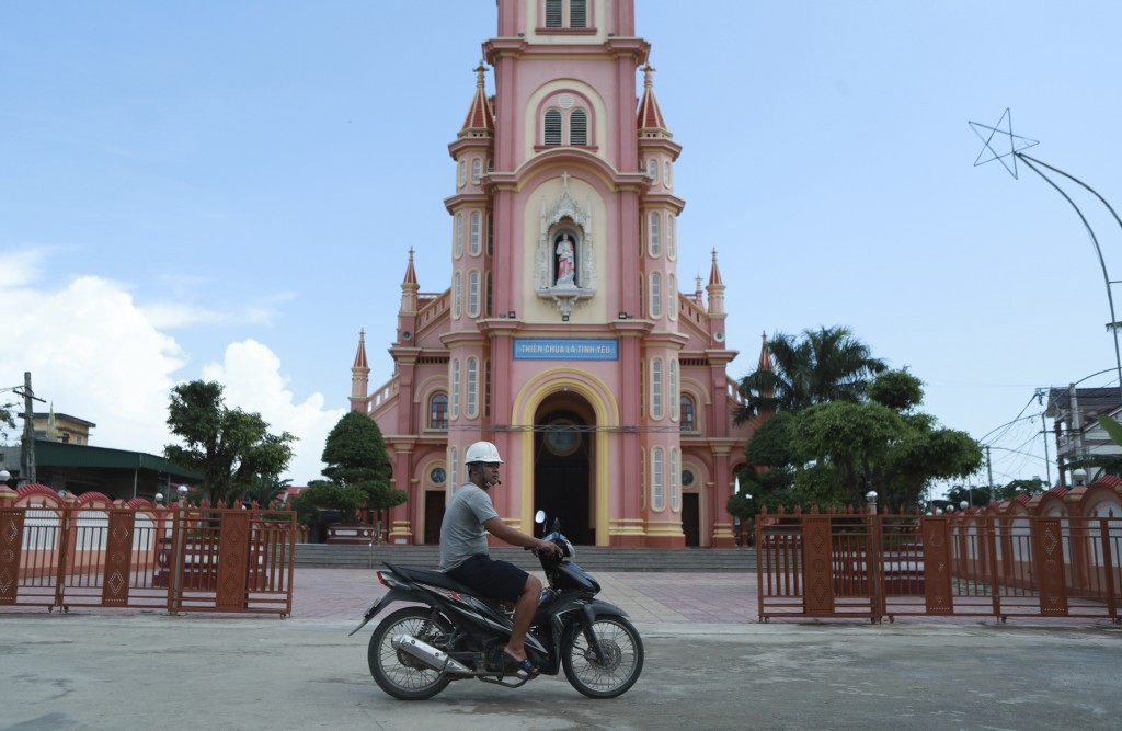 In this Oct. 28, 2019, photo, a man rides motorcycle past a church in Dien Thinh village, Nghe An province, Vietnam. Residents of this small rural com...