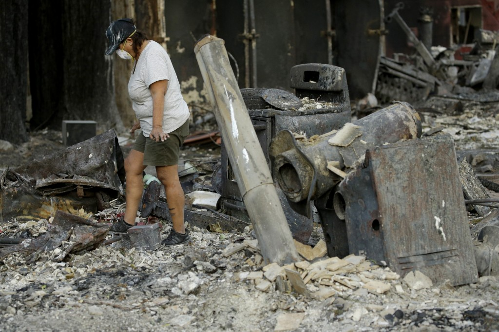 Bernadette Laos looks for salvageable items in her home that was destroyed by the Kincade Fire near Geyserville, Calif., Thursday, Oct. 31, 2019. (AP ...