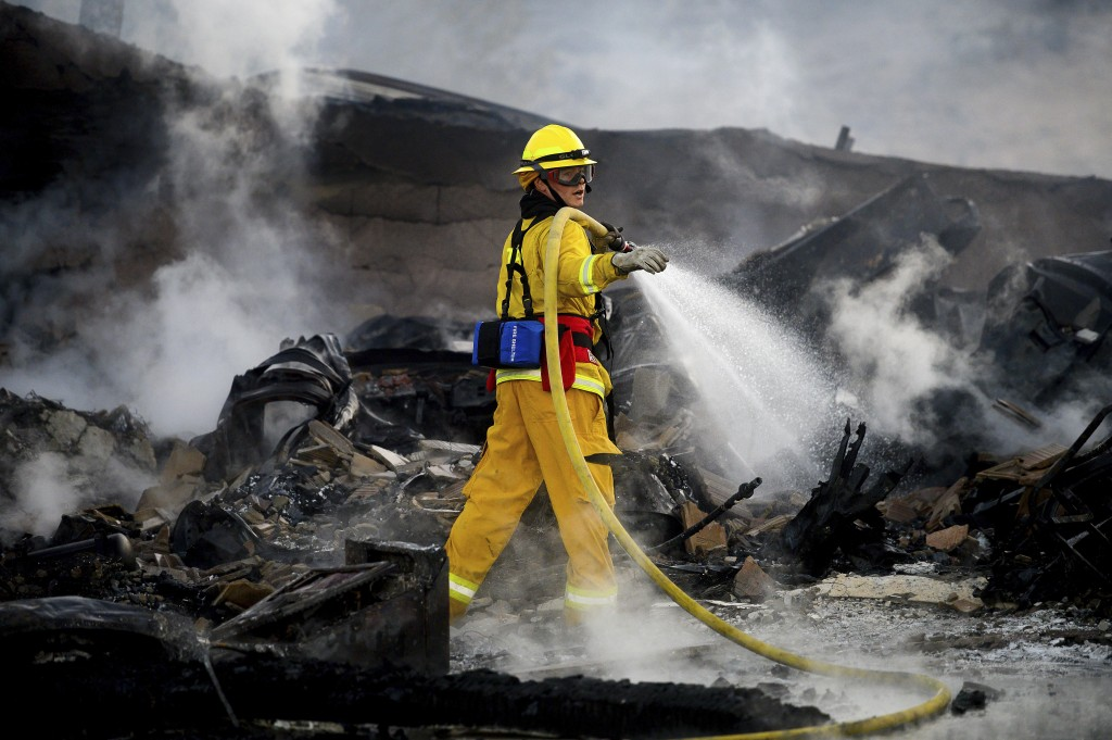 A firefighter sprays water on a leveled home as the Hillside Fire burns in San Bernardino, Calif., on Thursday, Oct. 31, 2019. Whipped by strong wind,...