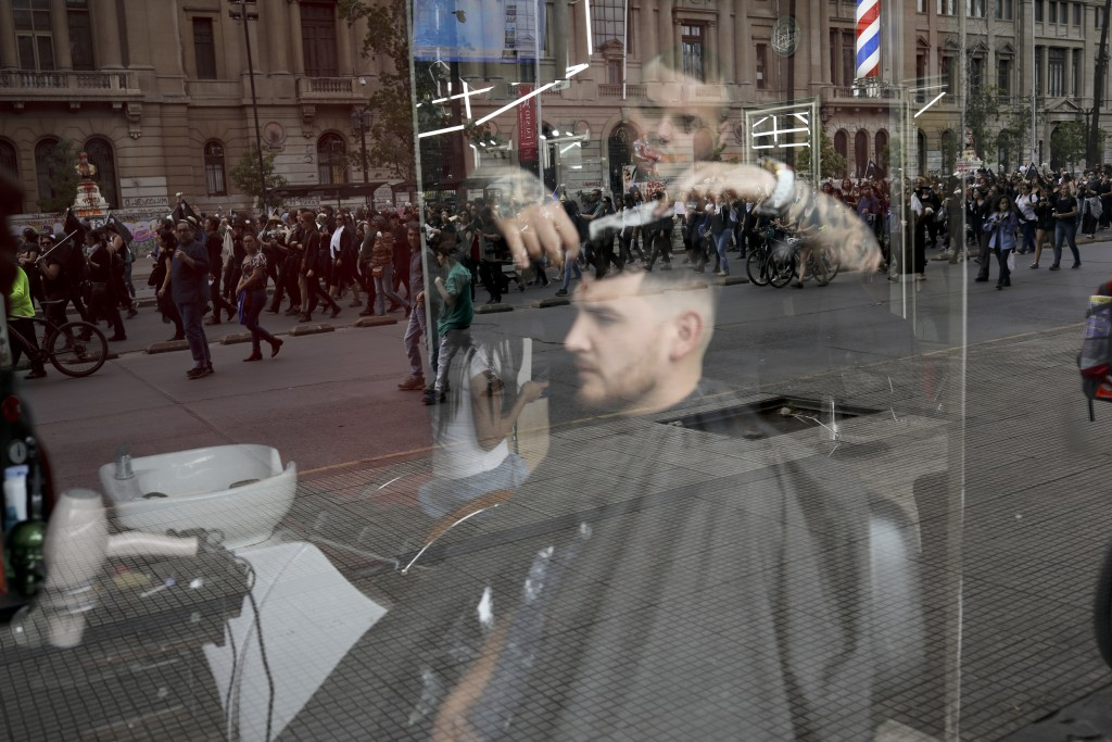 Anti-government demonstrators are reflected in the window of a hairdressing salon in Santiago, Chile, Friday, Nov. 1, 2019. Groups of Chileans continu...