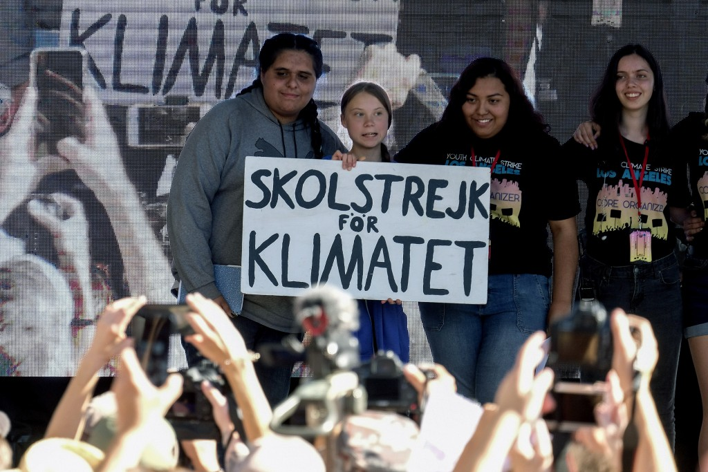 Climate activist Greta Thunberg, second from left, holding a sign, poses photos with other activists during a student-led climate change march in Los ...