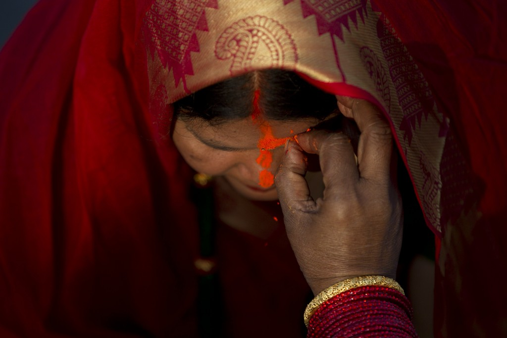 In this Saturday, Nov. 2, 2019, file photo, a Nepalese woman gets vermilion powder applied on her forehead after offering prayers to the setting sun a...