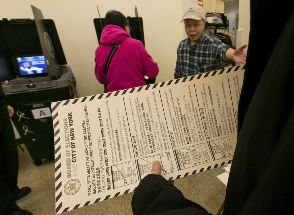 In this Nov. 4, 2014 file photo, a voter carries her ballot to be scanned at a polling place in New York's Chinatown neighborhood. A ballot measure wi...