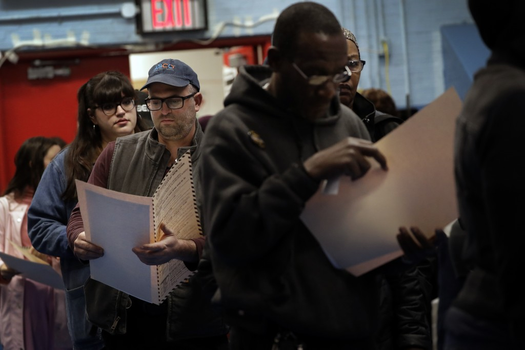 In this Nov. 6, 2018 file photo, voters read their ballot papers as they wait in line to cast their vote at P.S. 161 in Brooklyn borough of New York. ...