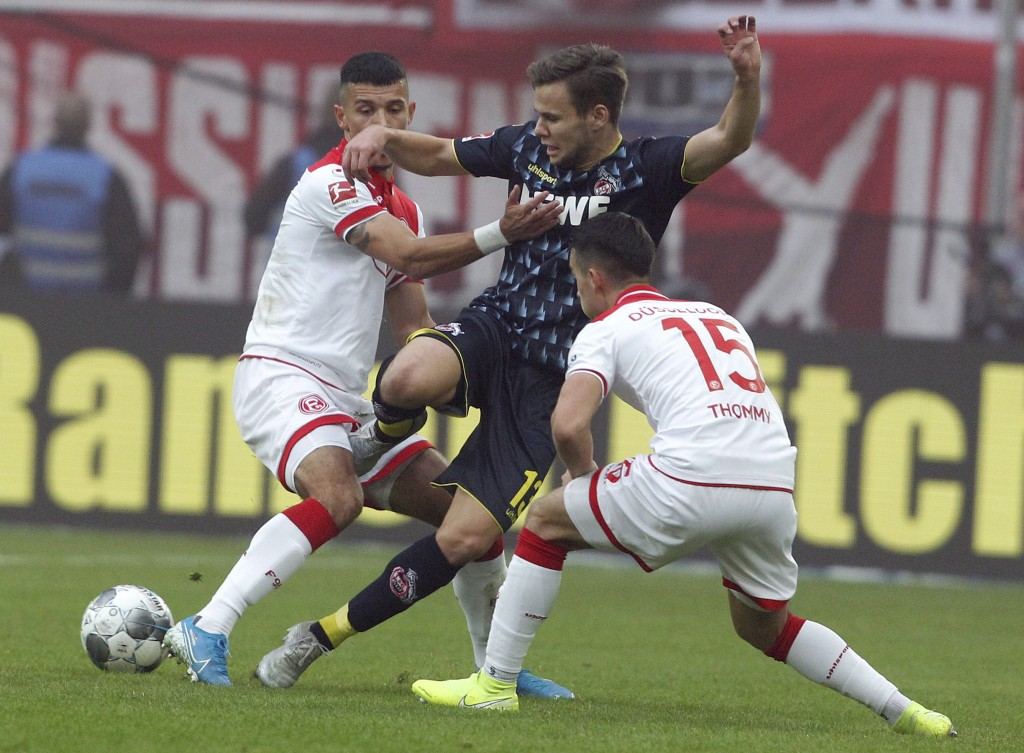 Duesseldorf's Alfredo Morales, left, and Erik Thommy, right, challenge for the ball with Cologne's Louis Schaub, center, during the German Bundesliga ...