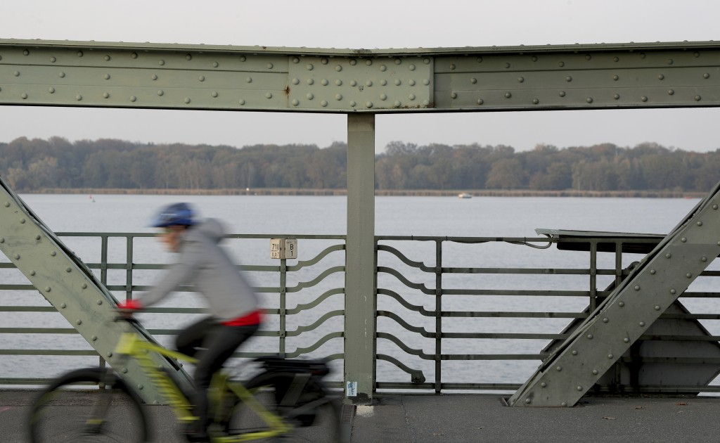 In this Wednesday, Oct. 23, 2019 photo a cyclist drives on the 'Glieniker Bruecke' (Glienicke Bridge) in Potsdam, Germany. During the Cold War, the Gl...