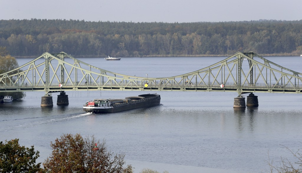 In this Wednesday, Oct. 23, 2019 photo a ship drives past the 'Glieniker Bruecke' (Glienicke Bridge) in Potsdam, Germany. During the Cold War, the Gli...