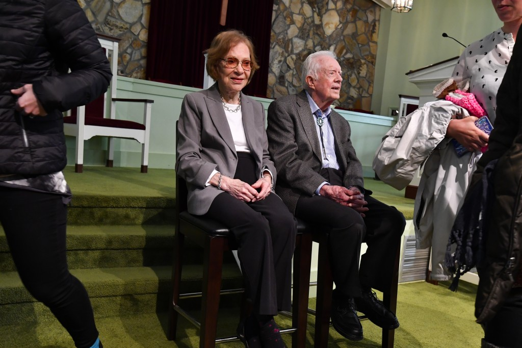 Former U.S. President Jimmy Carter and former first lady Rosalynn Carter, left, sit as guests of Maranatha Baptist Church come and go to have their ph...