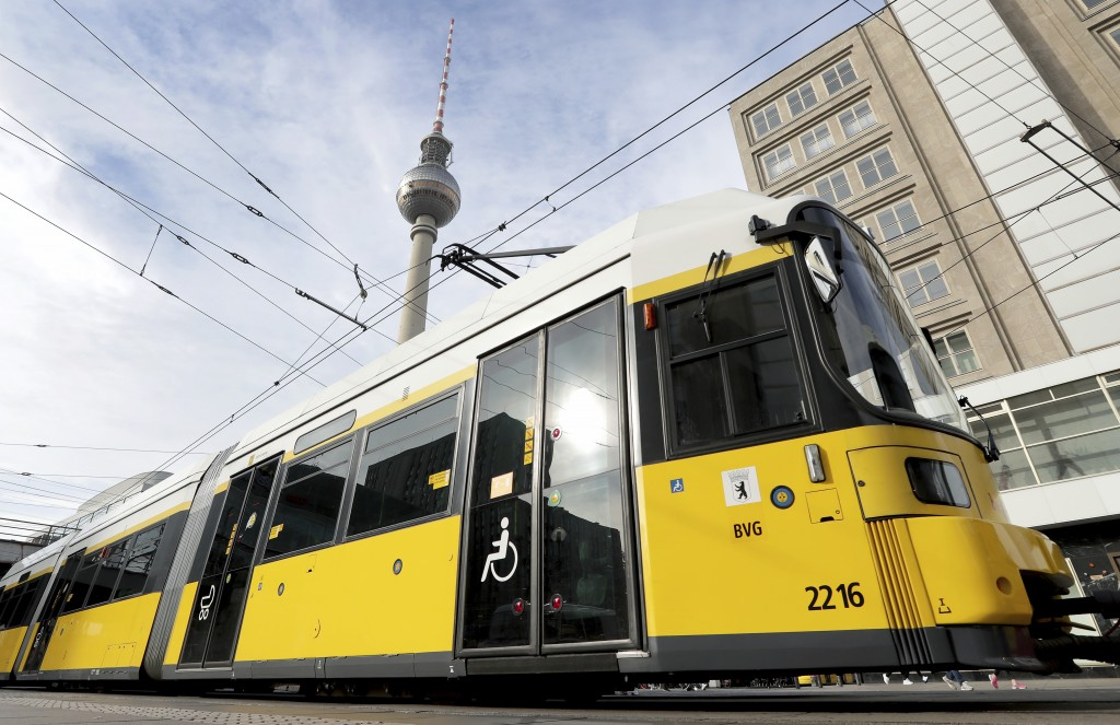In this Tuesday, Oct. 22, 2019 photo a street car drives in front of the Berlin TV Tower in Berlin, Germany. Berlin's complex public transport system ...