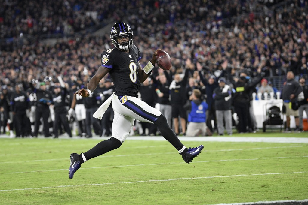 Baltimore Ravens quarterback Lamar Jackson scores on a run against the New England Patriots during the first half of an NFL football game, Sunday, Nov...