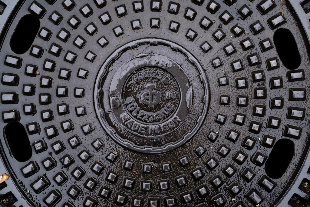 This Saturday, Nov. 2, 2019 photo, shows a manhole cover surviving from communist times in Berlin, when Volkseigene Betriebe, or Publicly Owned Enterp...