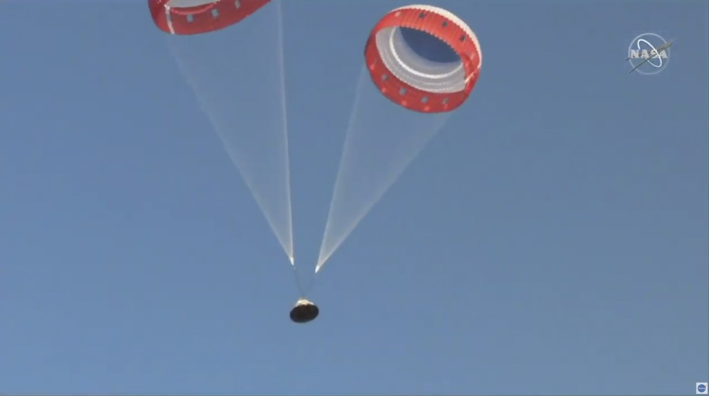 In this image made from a video provided by NASA  parachutes guide the Starliner capsule to the ground after a test of Boeing's crew capsule's launch ...