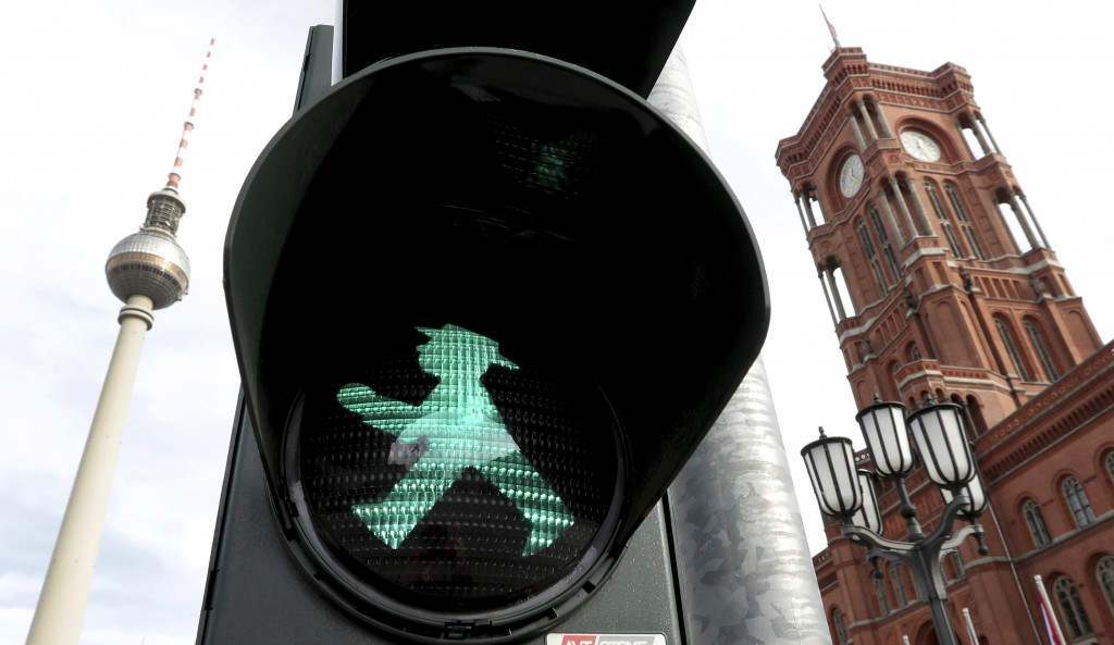 In this Tuesday, Oct. 22, 2019 photo a little traffic-light man is pictured in front of the Berlin TV Tower, left, and the 'Rotes Rathaus' (red townha...