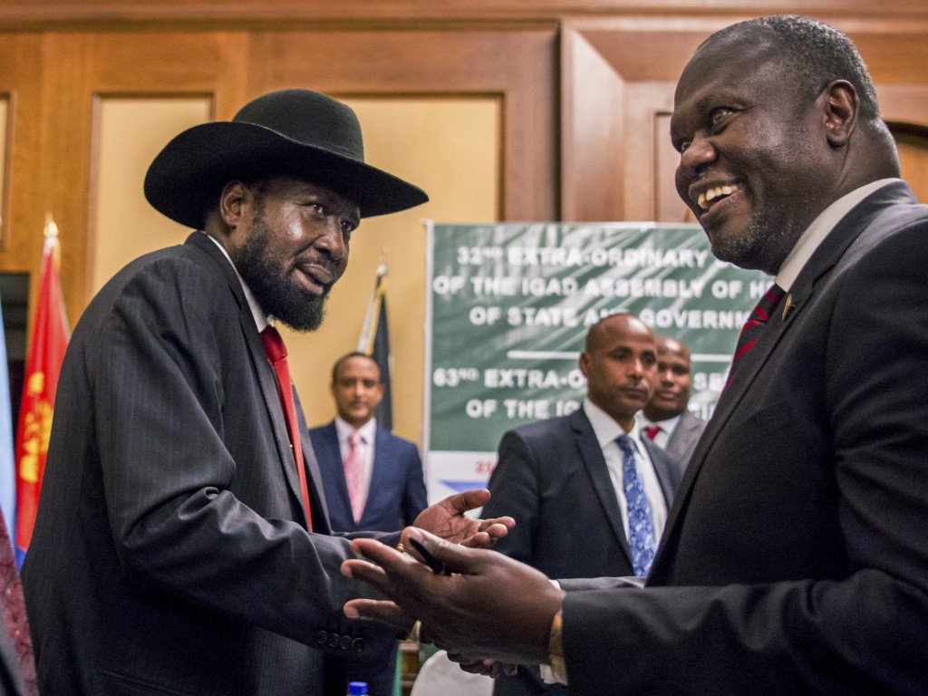 FILE - In this Thursday, June 21, 2018 file photo, South Sudan's President Salva Kiir, left, and opposition leader Riek Machar shake hands during peac...