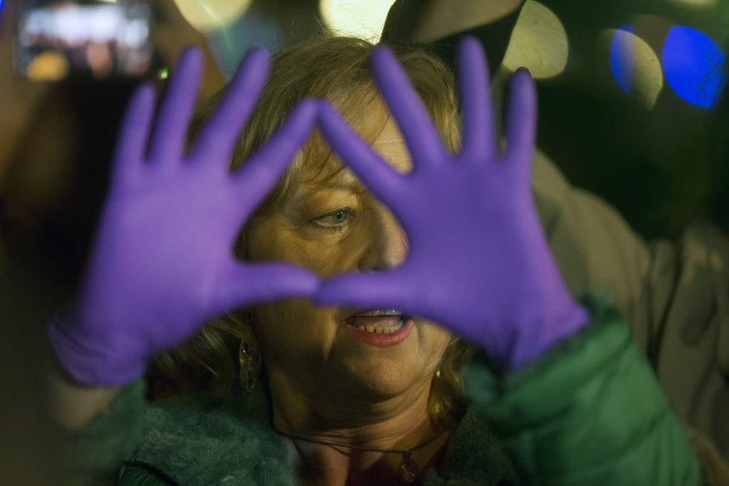 A woman holds up her hands outside the Justice Ministry in Madrid, Spain, Monday, Nov. 4, 2019. Thousands in Spain are demonstrating to demand changes...