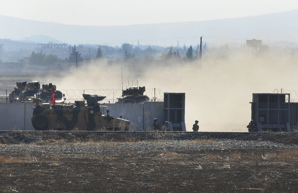 In this photo taken from the outskirts of the village of Mert Ismail near the town of Suruc, southeastern Turkey, Turkish army vehicles return to Tirl...