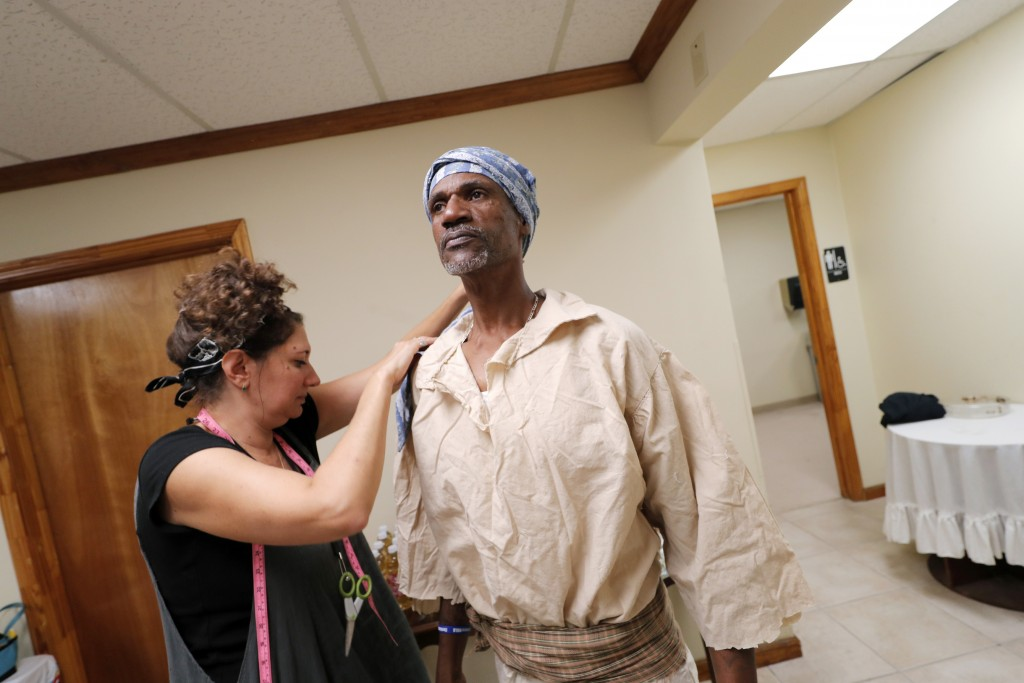In this Oct. 23, 2019, photo, reenactor Louis Ward is fitted for his period costumes by Patricia Gorman for the upcoming reenactment of a slave rebell...