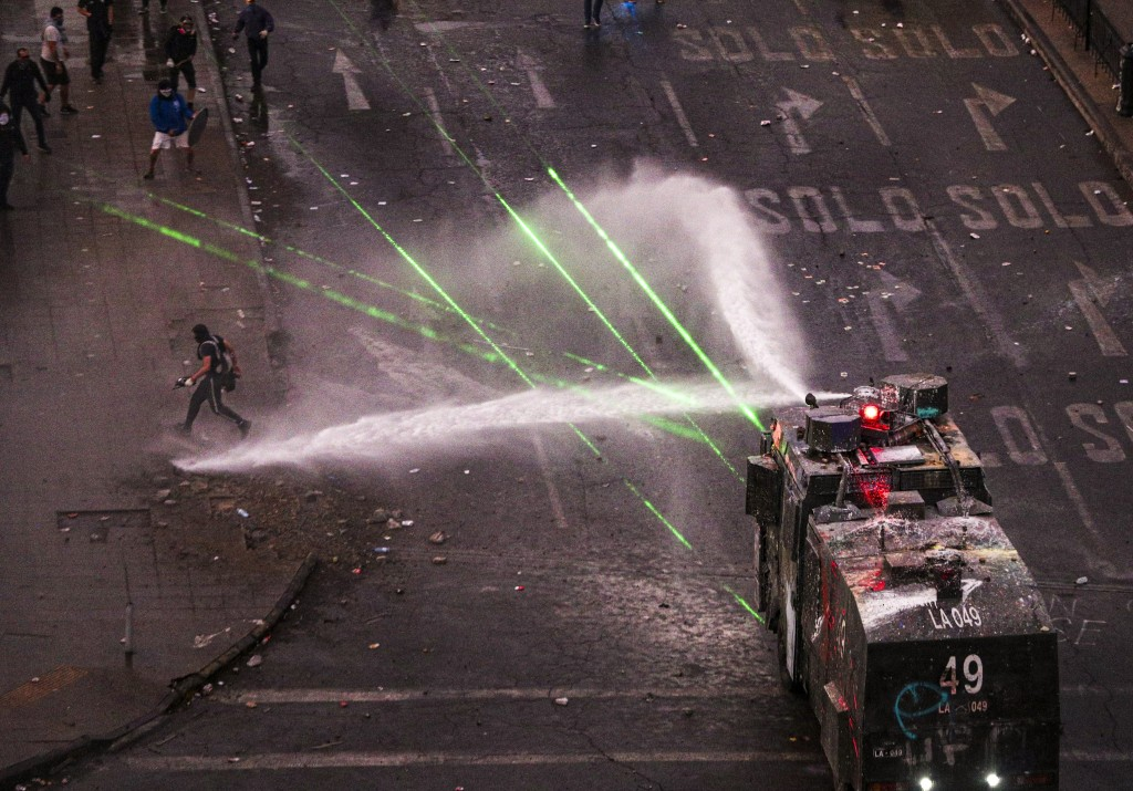Police water cannon advances on anti-government demonstrators during protest in Santiago, Chile, Monday, Nov. 4, 2019. Thousands of Chileans took to t...