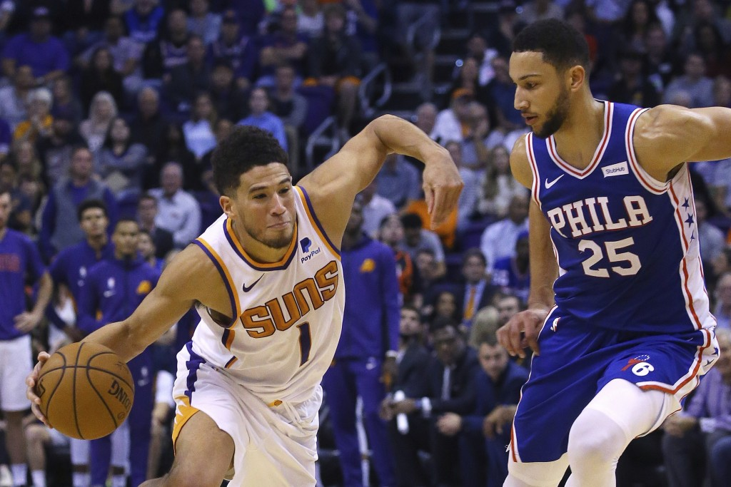 Phoenix Suns guard Devin Booker (1) drives past Philadelphia 76ers guard Ben Simmons (25) during the second half of an NBA basketball game, Monday, No...