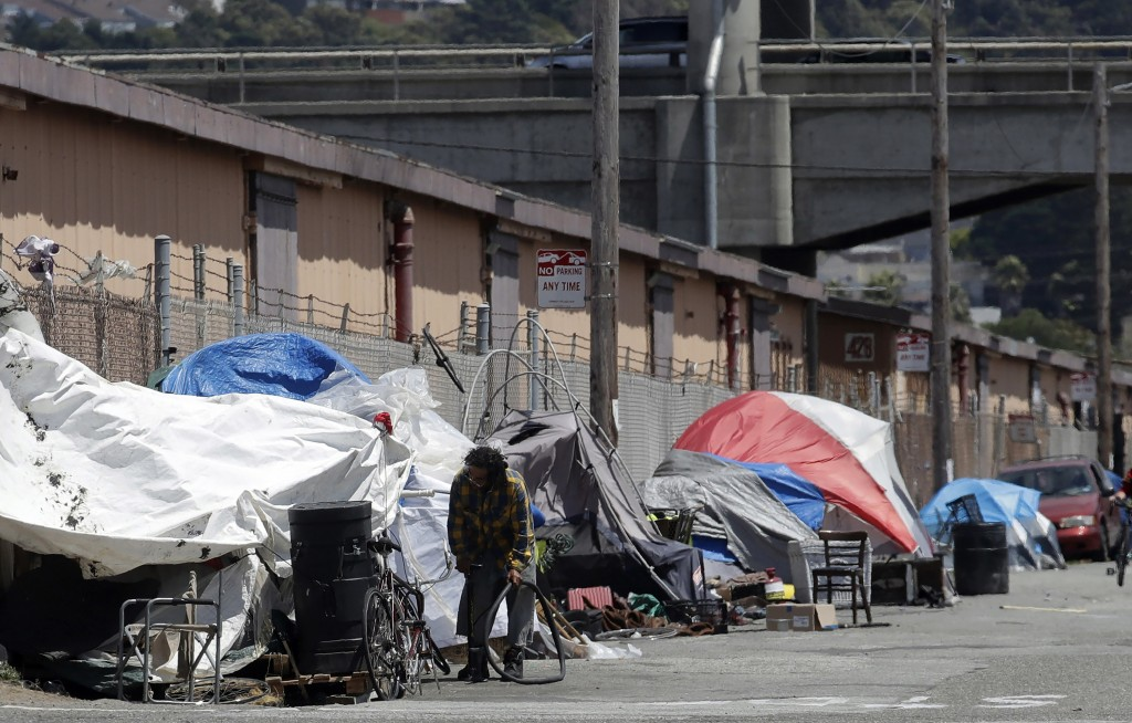 FILE - This June 27, 2019, file photo shows a man holding a bicycle tire outside of a tent along a street in San Francisco. Apple said Monday, Nov. 4,...