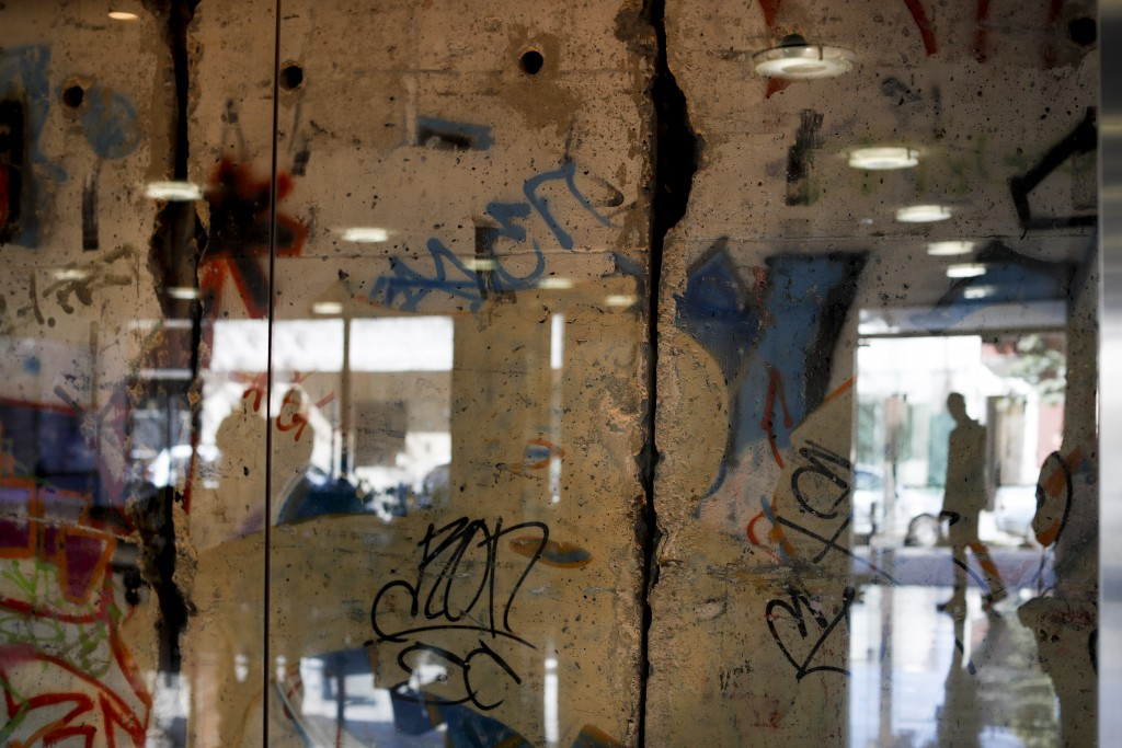 In this Thursday, Sept. 26, 2019 photo a man is reflected in a glass protecting a segment of the Berlin Wall at Editorial Perfil in Buenos Aires, Arge...