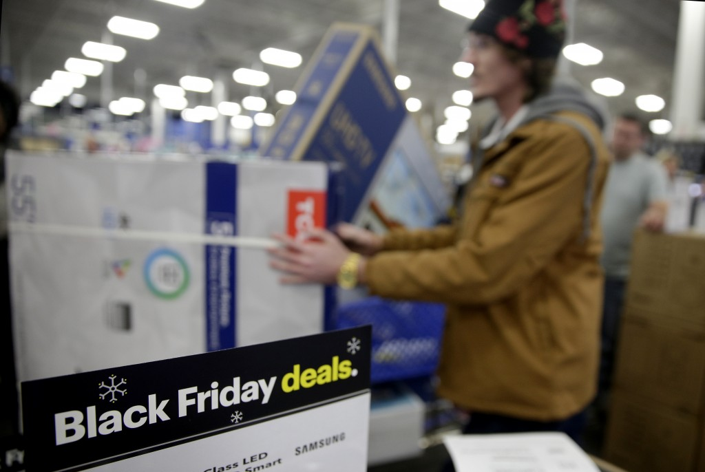 FILE - In this Nov. 22, 2018, file photo people wait in line to buy televisions as they shop during an early Black Friday sale at a Best Buy store on ...