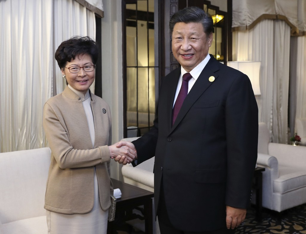 In this Monday, Nov. 4, 2019, file photo released by China's Xinhua News Agency, Chinese President Xi Jinping poses with Hong Kong Chief Executive Car...